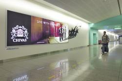 Chivas advertising campaign in Dubai International airport. Light boxes cast shadows of an alternative image.