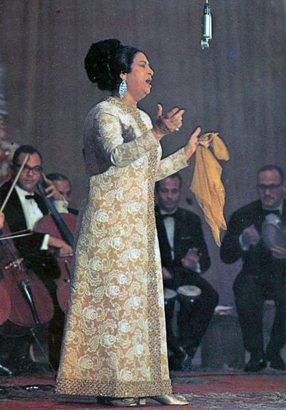 Umm Kulthum was the ultimate Muslim diva, seen here sporting a gold jacquard dress, chandelier earrings, beehive hairdo, and signature chiffon handkerchief.
