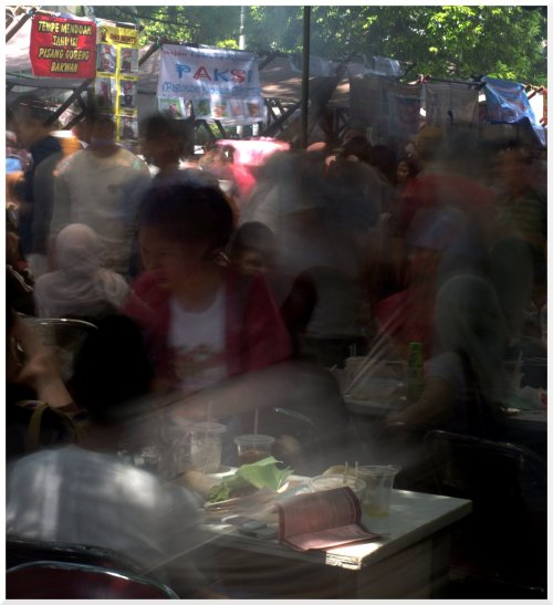 food crowd a girl managed to stay still in a hungry mob at the food stall at pasar seni. the place is unbelievably crowded, jammed and packed with families trying to sit while other order their food.