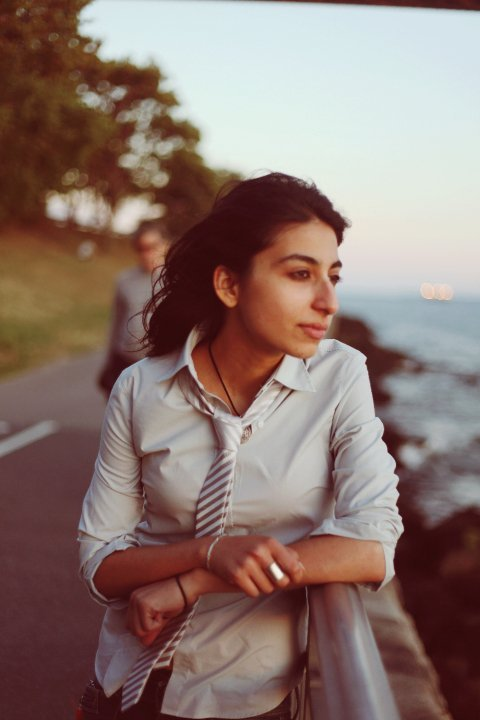 Arooj Aftab wears a simple sliver striped tie and the wind in her hair.