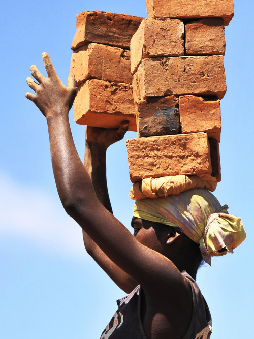 A woman transporting bricks
