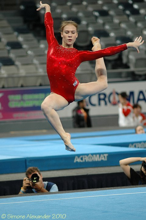 Ksenia Afanasyeva (RUS) at the 2010 Pacific Rim Championships. Lovely capture of a beautiful leap! Also, I like this leotard, very classy red with some bling! I hate that green one they started using now :( Photo credit goes to Simone Alexander!