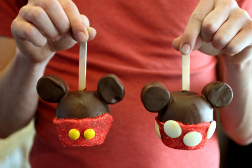 In honor of our upcoming honeymoon, I made- Disney Mickey & Minnie Chocolate Apples What you will need: 4 Granny Smith Apples 2 cups dark chocolate chips 1/2 cup vegetable oil 8 Large Marshmallows 8 toothpicks 4 Popsicle sticks Red sugar crystals Can of vanilla frosting 4 Yellow M & Ms (or jelly beans) 12 white chocolate discs Parchment paper Directions:  1. Attach marshmallows to apples securely with toothpicks. 2. Melt chocolate over in double boiler over simmering water & add oil and mix until incorporated. 3. Let chocolate cool slightly (enough to where it is no longer steaming) and dip each apple into chocolate to completely coat. Place onto parchment to cool.  4. When chocolate is completely cool and hardened, coat bottom half of apples with frosting, then attach m&ms and white chocolate discs to frosting.     5. Next, sprinkle the red sugar all over to coat all of the white frosting.   & voilà!!   Easy, fun, and yummy too!