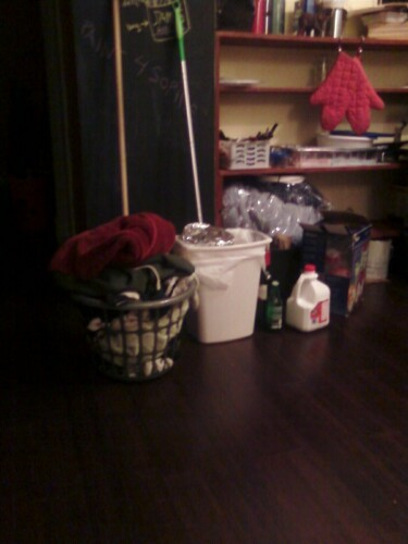 "So this is Ethan's laundry basket. Notice it is the size of our small trash can all of which you can compare to the gallon milk jug left on the ground.  In the two month's he's lived here this is the second load he's done, and his largest.  He wants clean clothes before moving into his new fancy crib yo!  the majority of the load is his 2 towels he has only washed once in the duration of his stay.  He's washing his hoodie he wears around the apartment and well, I can;t help but notice none of his jogging clothes, two green tees nor the brown paper bag filled with dirty socks are in here.  Where are his dirty boxers and other underwear?  Inquiring germaphobes (me) want to know! -Douche ""I feel itchy just thinking about him"" McGregor"