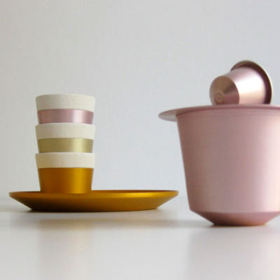 Upcycled coffee mugs and saucers made from recycled aluminum Nespresso capsules.  The Grand Crus Cup Parade, designed by Dottings, is a collection of coffee cups and saucers made from recycled aluminum Nespresso capsules. The design of the cups mimic the shape and colors of the capsules themselves, and could be purchased with points earned from returning used capsules to the company.  via Dear Coffee, I Love You.