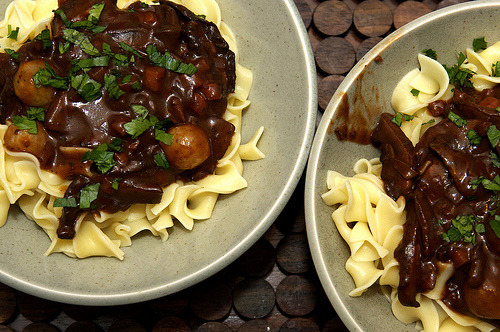mushroom bourguignon | smitten kitchen Hi!  This is Kelsey. And this is my first post here. And let me tell you: THIS RECIPE MIGHT CHANGE MY LIFE, AND YOURS.   Mushroom Bourguignon The best part about this — well, besides all of it, if I can so humbly say — is that it's a bourguignon without the heft of beef, but all of the indulgence. Plus, since you don't need to braise it in the oven for three hours, it can be a weekday night dinner. And you can serve it to vegetarians. And nobody will miss a thing. Serves 4 2 tablespoons olive oil2 tablespoons butter, softened2 pounds portobello mushrooms, in 1/4-inch slices (save the stems for another use) (you can use cremini instead, as well)1/2 carrot, finely diced1 small yellow onion, finely diced2 cloves garlic, minced1 cup full-bodied red wine2 cups beef or vegetable broth (beef broth is traditional but vegetable to make it vegetarian; it works with either)2 tablespoons tomato paste1 teaspoon fresh thyme leaves (1/2 teaspoon dried)1 1/2 tablespoons all-purpose flour1 cup pearl onions, peeled (thawed if frozen)Egg noodles, for servingSour cream and chopped chives or parsley, for garnish (optional) Heat the one tablespoon of the olive oil and one tablespoon of butter in a medium Dutch oven or heavy sauce pan over high heat. Sear the mushrooms until they begin to darken, but not yet release any liquid — about three or four minutes. Remove them from pan. Lower the flame to medium and add the second tablespoon of olive oil. Toss the carrots, onions, thyme, a few good pinches of salt and a several grinds of black pepper into the pan and cook for 10, stirring occasionally, until the onions are lightly browned. Add the garlic and cook for just one more minute. Add the wine to the pot, scraping any stuck bits off the bottom, then turn the heat all the way up and reduce it by half. Stir in the tomato paste and the broth. Add back the mushrooms with any juices that have collected and once the liquid has boiled, reduce the temperature so it simmers for 20 minutes, or until mushrooms are very tender. Add the pearl onions and simmer for five minutes more. Combine remaining butter and the flour with a fork until combined; stir it into the stew. Lower the heat and simmer for 10 more minutes. If the sauce is too thin, boil it down to reduce to the right consistency. Season to taste. To serve, spoon the stew over a bowl of egg noodles, dollop with sour cream (optional) and sprinkle with chives or parsley.