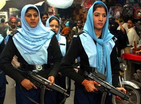 These are Pakistani policewomen. The lady on the right is wearing delicate henna on her hands, and both submissive Muslim women are wearing a girlish lace-trim on their encumbering headscarves.