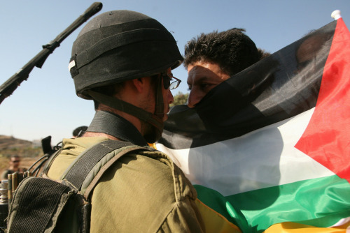 2morrowland:  A Palestinian protester holding his national flag confronts an Israeli soldier during a demonstration against Israel's separation barrier in the West Bank village of Maasarah near Bethlehem on November 12, 2010. (MUSA AL-SHAER/AFP/Getty Images) #