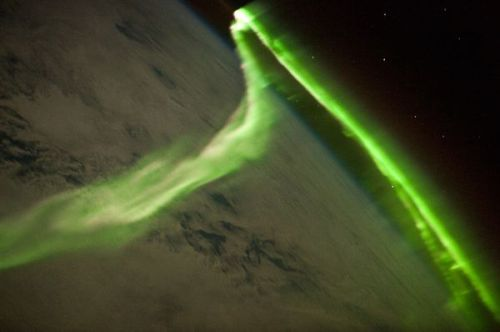 Aurora Australis from space. The Auroras Borealis and Australis occur when charged particles streaming from the Sun (a.k.a the solar wind) interact with Earth's magnetic field, resulting in collisions with atoms of oxygen and nitrogen in the upper atmosphere.