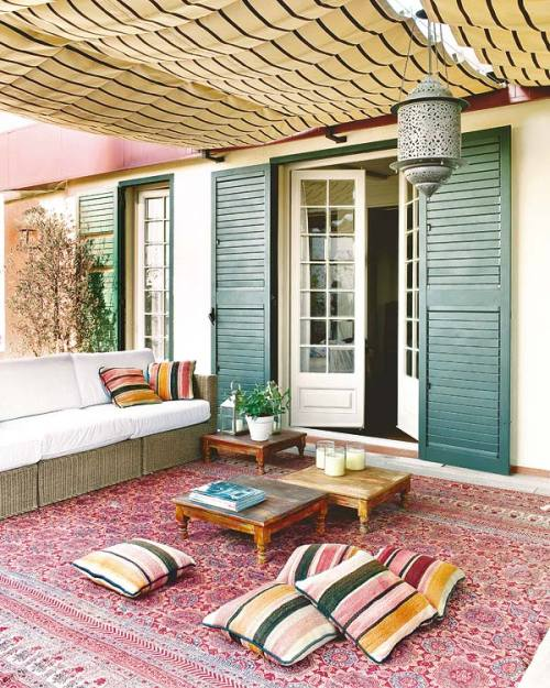 that rug and that lantern. yes. and better throw in the striped canopy. justbesplendid:  porch (via)