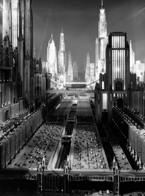1930s imagining of 1980s New York via the sci-fi musical Just Imagine (1930, dir. David Butler) More on the building of the set here. The opening scenes of the film, which feature this cityscape, can be seen here. Buildings 250 stories high!…traffic on nine levels…rockets that shoot from star to star…airplanes that land on the roofs of buildings…a whole meal in a capsule that can be swallowed in one gulp… No — this isn't a Jules Verne dream induced by a Welsh rarebit. It's New York in 1980, as foretold in the new Fox picture, Just Imagine! In 1980, people have serial numbers, not names, marriages are all arranged by the courts…Prohibition is still an issue…Men's clothes have but one pocket. That's on the hip…but there's still love! Don't laugh! Our grandaddies laughed at the thought that men might fly! Fantastic? Certainly—but stranger things have come to pass than those which have been portrayed in this dream of New York of A.D. 1980! -excerpted from Just Imagine's promotional campaign materials, reprinted in Ruth Waterbury's Photoplay: The aristocrat of motion picture magazines