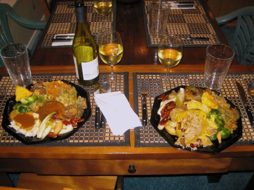"Happy Thanksgiving from reader Andi, who writes that her vegan potluck was ""bomb dot com. Two types of stuffing, Tofurky, maple chipotle glazed Field Roast, brussels sprouts, sweet potatoes with Dandies marshmallows, stuffed acorn squash, sweet potato knishes, pear and endive salad with candied pecans, butternut squash and mushroom tart, green bean casserole, and mashed potatoes with gravy. For dessert? A layered chocolate and vanilla crème brûlée custard, pumpkin pie, and baked apples with Soy Whip!"" And that would explain the place settings at what is clearly a desk, and why those two plates are piled obscenely high with food. Andi and friends, your potluck gets the Vegansaurus stamp of gluttonous approval. We are so, so proud of you. Happy Thanksgiving!"