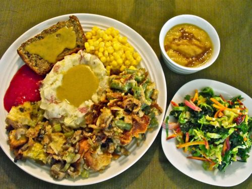 "Happy Thanksgiving from Erin of Vegan Homemade! She had so much food she needed extra plates just for dinner! On the main plate is, clockwise from top left, nut roast extraordinaire, corn, green bean casserole, oyster mushroom stuffing, orange-cranberry sauce, and in the center,  mashed potatoes and ""turkey"" gravy. In the upper right corner, a bowl of chestnut and celeriac soup with sherry-cider reduction; in the lower right, chopped salad with ""honey""-lemon poppyseed vinaigrette. Whoever got to share in that bounty is extremely lucky! Happy Thanksgiving, Erin!"