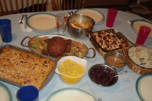 "Happy Thanksgiving from reader Sonni! She threw a post-Thanksgiving dinner party for her friends, because, as she puts it, ""most of our families aren't very vegan/veggie friendly (or are just plain crazy)."" On the table here is mac 'n' cheez, Tofurky with gravy, stuffing, garlic mashed potatoes, veggies, and cranberry sauce, plus another friend's candied yams. Those are good friends to have. Happy post-Thanksgiving, Sonni!"