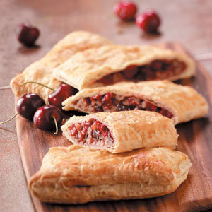 Easy Cherry Strudels Recipe 10 Servings / Prep: 15 min. Bake: 20 min. Ingredients: 1 can (14-1/2 ounces) pitted tart cherries 1 cup sugar 1/2 cup dried cranberries or raisins 1 tablespoon butter 3 tablespoons cornstarch 1-1/2 cups chopped walnuts 1 package (17.3 ounces) frozen puff pastry, thawed 1 egg, lightly beaten Directions: Drain cherries, reserving 1/3 cup juice. In a large saucepan, combine the cherries, sugar, cranberries and butter. Cook and stir over medium heat until heated through. Combine cornstarch and reserved juice and add to the pan. Bring to a boil. Cook and stir 1-2 minutes longer or until thickened. Remove from the heat; stir in walnuts. Unfold one pastry sheet and cut in half. Mound half of the cherry mixture on one pastry half to within 1/2 in. of edges. Top with remaining pastry half; pinch edges to seal. Repeat with remaining pastry and filling. Place on a greased foil-lined baking sheet. With a sharp knife, cut diagonal slits tops of strudels; brush with egg. Bake at 400 degrees for 20-25 minutes or until golden brown. Yield: 2 strudels (5 slices each). Nutrition Facts: 1 slice equals 506 calories, 25 g fat (5 g saturated fat), 24 mg cholesterol, 180 mg sodium, 65 g carbohydrate, 5 g fiber, 9 g protein.
