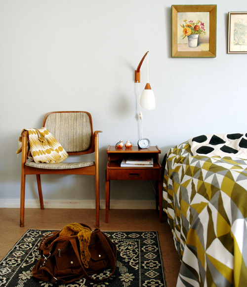 Loads I like in this one.  There's those up-off-the-table bedside lamps I've mentioned  before  on this blog.  I also love the mismatched bedcovers, the chair, and the little flower painting.  I absolutely love little flower paintings. Nice handbag too!
