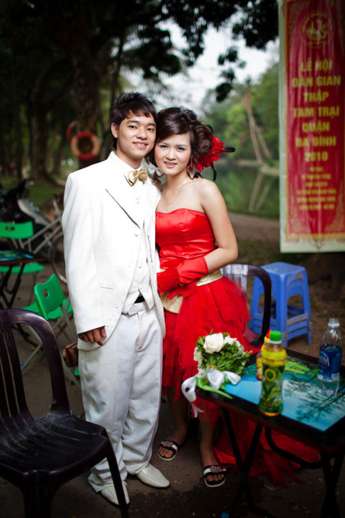 06 March, 2010 | A newlywed couple prepare for a photoshoot at the Botanical Gardens in Hanoi, Vietnam.  As in China, the newfound middle class and nouveau-riche in Vietnam have ignited a boom in the wedding industry the past few years. Weekends at the park, or by the Opera House, (or other such city landmarks) can see dozens of couples having their engagement photos done at the same time. And some of those outfits are truly spectacular. And hopefully unique.