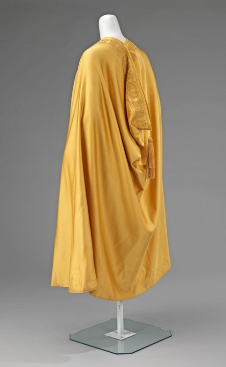 "Liberty & Co. of London evening cape ca. 1900-1910 via The Costume Institute of The Metropolitan Museum of Art ""Produced in one of Liberty's trademark high-quality silks, the rich yellow satin of this cape is draped in the fashion of Middle Eastern outerwear. Its elegant simplicity is relieved by the distinctive curvilinear pattern of overlapping silk cord that sinuously loops around itself. It is a good early 20th-century example of the Art Nouveau design that was synonymous with Liberty & Co."""