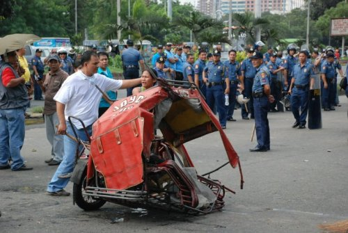 culture-shock-pigments:  Police brutality in the Philippines. I can't help not to cry while viewing the dispersal pictures from yesterday. Short background: The City Government of Manila issued an ordinance prohibiting motorized pedicabs or kuliglig's from taking main routes. In response, the drivers and operators of said transport held a picket in front of Manila City hall in protest of said ordinance. This is the Manila City Hall's response. Photo courtesy of Derek Firmeza