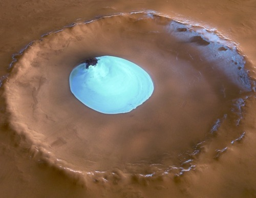 unknownskywalker:  Ice lake on Mars This is a giant patch of frozen water inside an unnamed impact crater on Mars. The existence of this water-ice patch on Mars makes life a more likely possibility and raises the prospect that past or present life will one day be detected. The crater with ice disc is on the Vastitas Borealis, a broad plain that covers much of Mars's far northern latitudes. The crater is 35 km wide, with a maximum depth of about 2 km. The image was taken by the High Resolution Stereo Camera on ESA's Mars Express. Scientists believe the water-ice is present all year round because the temperature and pressure are not sufficient to allow it to change states and vaporise into the atmosphere. It is not frozen carbon dioxide, because this type of ice had already disappeared from the north polar cap by the time this image was taken. • Source: European Space Agency (Flickr)