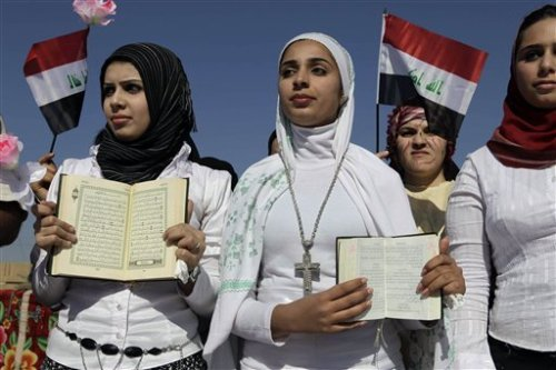 In Baghdad, a Muslim woman (in black hair covering and holding a copy of the Quran) stands in solidarity with a Christian woman (in white hair covering and holding a copy of the Bible), to show solidarity with the dwindling number of Iraqi Christians and their right to live freely and peacefully side-by-side with their Muslim sisters and brothers.