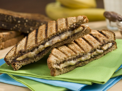Grilled Banana and Nutella Panini Cook: 10 min / Yield: 6 servings Ingredients: 3 ripe bananas, sliced 12 slices whole-wheat bread 1 cup chocolate-hazelnut spread (recommended Nutella) 16 tablespoons unsalted butter, softened 3 tablespoons confectioners' sugar Directions: Place the bananas in a bowl and mash until smooth. Place the slices of bread on a flat surface and spread each slice with some of the hazelnut spread. Spread the mashed banana over 6 of the slices and combine the slices to make 6 sandwiches. Heat grill to medium-high. Spread 1 side of the each sandwich with some of the butter and place on the grill, buttered-side down. Grill until golden brown. Spread the remaining butter on the bread facing up, flip over and continue grilling until golden brown. Remove from the grill and sprinkle with the confectioners' sugar. Eat immediately.
