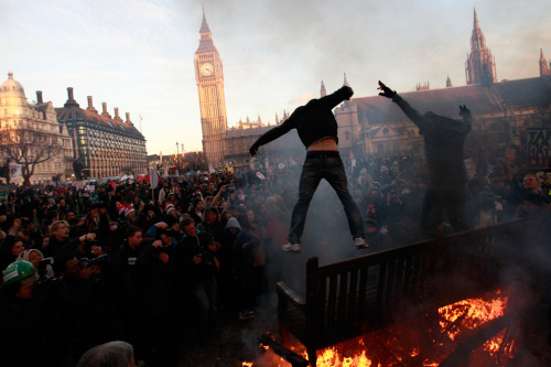 p3p510:  Demonstrators jump off burning park benches during a protest outside the Houses of Parliament in Westminster, central London December 9, 2010. (REUTERS/Andrew Winning)