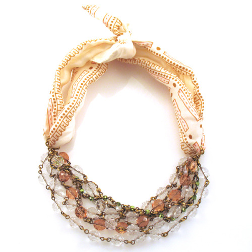 "Scarf Necklace This uses a vintage scarf, Czech glass beads, and vintage brass chain. Doesn't brass turn your skin green? It's one of a kind, but still….$240 (plus shipping)? Definitely a good ""I can make that"" craft candidate. Cut an old scarf in two longwise. Sew the raw cut edge to the opposite edge to make a long tube then turn it right-side out. Fold the tube in half and put a piece of chain (not brass) around the middle of the tube. Join chain together into a ring. Hang beads from the ring of chain. Repeat for the other side. Tie the scarf ends around your neck (it can be worn as a choker or longer length, depending on how you tie the scarf). Ta da! You just saved $240 plus shipping!"
