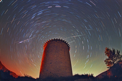 inothernews:  SLINGS, NOT ARROWS   At least five meteors, part of the annual Leonid meteor shower, are photograhed streaking high above the Torre de la Guaita, an observation tower used during the 12th century in Girona, Spain.  (Photo: Juan Carlos Casado / TWAN via NASA APOD)