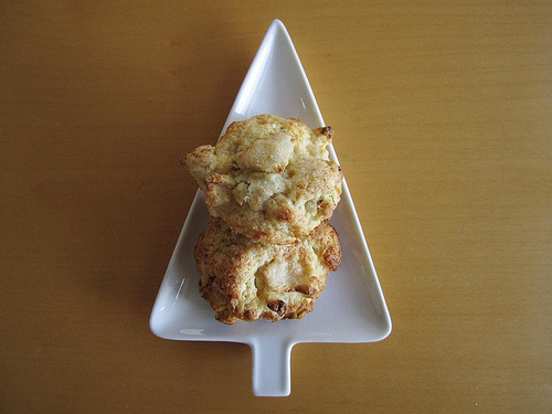 This Christmas I'm leaving my new favorite roasted apple cheddar scones for Santa. p.s. I'm Santa.Roasted Apple Cheddar Scones(adapted from The Perfect Finish via Smitten Kitchen)  Makes about a dozen.2 Granny Smith apples1.5 c. flour (I used spelt)1/4 c. sugar + more for sprinkling1.5 tsp. baking powder1/2 tsp. salt6 TB cold butter, cut into small pieces1/2 c. white cheddar, finely grated1/4 c. heavy cream + more for brushing1 eggWhisk flour, sugar, baking powder, and salt together in a bowl.  Rub in the butter by hand until the mixture resembles a coarse meal.  Stir in the cheddar.  Stick this in the fridge or freezer while you roast the apples.Preheat oven to 375ºF and line a baking sheet with parchment paper.  I peeled half of my apples, but next time I'm leaving all the skin on.  Chop the apples into small chunks.  Roast for 15-20 minutes, until they are barely starting to color.  Let cool.  Reuse the parchment paper to bake the scones.Take the bowl out of the fridge.  In a small bowl, whisk together the cream and egg.  Make a well in dry ingredients, pour in the wet.  Give this a few gently folds with a spatula, then a few more as you add in the apple.  Do not overmix.  I used a quarter cup measure to scoop and form the scones.  You can also pat the dough into a circle and cut wedges.  Place them on the baking sheet, brush the tops with cream, and sprinkle with sugar.  Bake until golden brown, 20-30 minutes.  Cool for 10 minutes before eating.