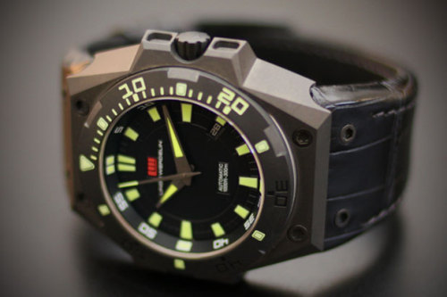 "Watchmakers Linde Werdelin present their first US Limited Edition  timepiece – the Hard Grey DLC (Diamond Like Carbon ). The ""Hard"" series  is based on the brand's original ""The One"" model, but bears a different  bezel, hands, color and dial to create a unique allure. The new Hard  Grey also features a vivid color contrast between the red logo and the  bright yellow hands & luminous hour markers. Most notably, the case  is produced in a DLC grey coating unlike any Linde Werdelin previously  made. It shares the same case dimensions as the rest of the Linde  Werdelin watch line to ensure the safe attachment of both The Rock and  The Reef instruments for extreme skiing and diving respectively. Only 11  pieces were produced, currently available for pre-order through Exquisite Timepieces, priced at $7,300 USD."