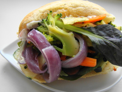 Vegan Banh Mi 3  cups arugula 1/2 sliced bell pepper 1/2 cucumber, sliced 1/2 cup steamed broccoli 1/2  cup  diced carrots 1/2  cup  rice vinegar 1/2  teaspoon  salt 1  teaspoon agave 1/3 cup thickly sliced red onion 1 diced jalapeno pepper  tablespoon  lime juice 1  tablespoon  chopped fresh ginger 2  teaspoons  chopped garlic 1/2  teaspoon  Chinese five-spice powder About 4 tsp. Asian chili paste 3 cups sliced tofu 4 small baguettes Handful Sliced Red Grapes 1/4  cup  minced cilantro leaves Vegan Mayo In a bowl toss the veggies with the vinegar, agave and salt. Combine the rest of the seasoning with the onion, peppers, and lime juice- marinade the tofu an hour then fry in olive oil. Drain. Slice the baguettes, slather with mayo, add the cilantro, grapes and tofu. Pile on the veggies and serve. Serves 4.