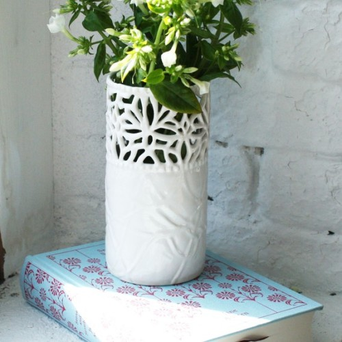 There are containers that can hold flowers. Then there are vases. Beautiful vases. This one is milky white porcelain with hand carved lattice detail at the top. By Isabelle Abramson.