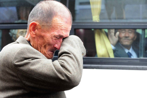 A North Korean man (right) on a bus waves his hand as a South Korean man weeps after a luncheon meeting during inter-Korean temporary family reunions at Mount Kumgang resort October 31, 2010. Four hundred and thirty-six South Koreans were visiting North Korea to meet their 97 North Korean relatives, whom they have been separated from since the 1950-53 war, for three days. (REUTERS/Kim Ho-Young)