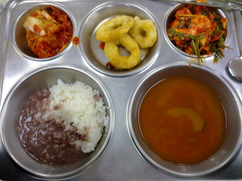 "Clockwise from top left: kimchi; calamari rings with soy sauce; sliced mushrooms and Korean chives in gochujang sauce; generic ""Korean"" vegetable soup; rice and patjuk (red bean porridge).  As you may see from clicking the patjuk link, patjuk is eaten to commemorate the winter solstice."