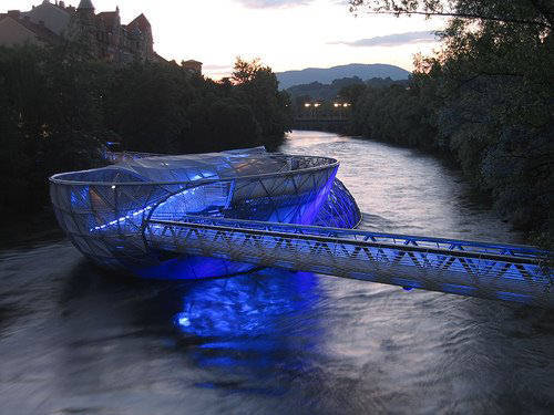 Designed by New York architect Vito Acconci, the Aiola Island Bridge in  Graz, Austria bridges the banks of the Mur River. The glassy structure,  which opened in 2003, also houses a bar, a sunbathing area and a coffee  house.   9 of the other most beautiful bridges in the world.