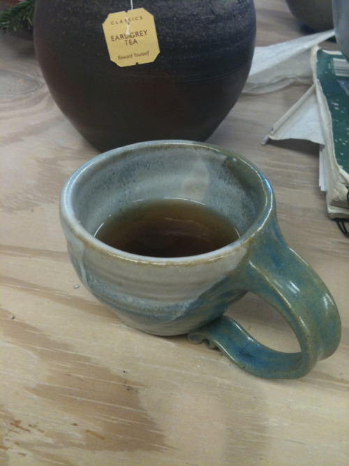 My First Thrown and glazed tea cup. Feels light to the hand, fits properly around the face for those of us who have larger noses, comfortable handle and lovely blue.  tea cup. 2010. glazed stoneware
