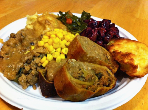"This is reader BW's plate from Christmas day! BW says that ""Some [dishes were] made by me, some made by family with my input on veganization. Going clockwise, starting at the bottom, is a seitan roulade I made filled with shiitake mushroom and vegan sausage stuffing. Then a huge helping of said stuffing and mashed potatoes covered in Tofurky-brand gravy because it's easy and yummy. Then collards with tomatoes. Then a ridiculous garlicky beet salad, then a vegan version of this thing called ""The Bread"" which is basically a decent loaf of bread SMOTHERED in butter or in my case Earth Balance and broiled till it turns into something magical and delicious. In the center is corn!"" Isn't it lovely when omnivorous families make vegan food for you, freaky hippie meat-forbearing children? Also, if anyone wanted to make me The Bread sometime, I would NOT turn it down. DANG."