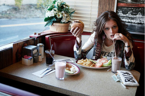 Pretty girls eat burgers while drinking chocolate milkshakes.