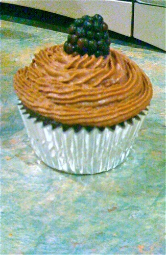 "Reader Devin ""finally tried a recipe from Vegan Cupcakes Take Over the World,"" which effort resulted in this chocolate cupcake with chocolate mousse frosting and a blackberry topping! Devin says ""it came out fantastic, and the omnivore family members loved it!"" It is one adorable cupcake! [Are you making something special for new year's? Send us a photo!]"
