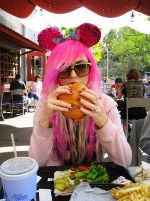 Pretty girls eat burgers with pink hair.