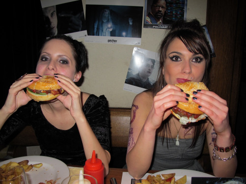 Pretty girls eat burgers in front of Harry Potter pictures.