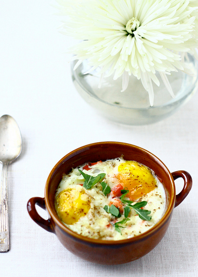Baked Eggs with Smoked Salmon Ingredients: 8 medium eggs (503) 1.5 cups diced leeks, white and pale green parts only (81) 1.5 cups chopped arugula, plus a little extra for garnish (10) 4 ounces smoked salmon, cut into small cubes (133) 2/3 cup grated fat free Parmesan(107) 4 tablespoons grated fat free Parmesan, for garnishing (40) 1 tablespoon olive oil (119) Freshly ground pepper to taste (5) Method: 1) Preheat oven to 400 degrees. 2) Warm a saute pan over medium-low heat. Add the oil. When hot, add the leeks and saute until just soft, about 4 or 5 minutes. Turn heat off, but keep the leeks in the pan. Add the arugula and stir, allowing the greens to wilt. 3) Grease the four ramekins. Divide the leek/arugula mixture evenly between them. Repeat with the salmon, adding about one ounce to each container in a thin layer over the greens. Next, divide the cheese amongst the four, also in a thin layer, over the salmon. 4) Carefully crack two eggs into each ramekin, taking care to not break the yolk. Atop the eggs, sprinkle each with a tablespoon of Parmesan and finish with a few twists of the pepper mill. 5) Place the ramekins on a shallow baking sheet and bake until the whites have set, about 12-15 minutes. 6) When they are ready, let them rest for a couple minutes- they'll be too hot to eat immediately! 7) Garnish with a little more chopped arugula and serve. This makes four servings, each having 250 calories. This might work with only one egg per serving, in which case said serving has 187 calories.