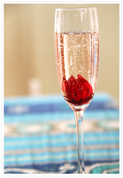 Sparkling Hibiscus Champagne Cocktail   1 wild hibiscus flower Champagne or Prosecco    Directions  Position the hibiscus flower at the bottom of a champagne flute and slowly fill it with your favorite bubbly. As the champagne fizzles, the hibiscus flower will open up and bloom in your glass. Once you drink your bubbly, refill it. Or, just nibble on the edible flower.