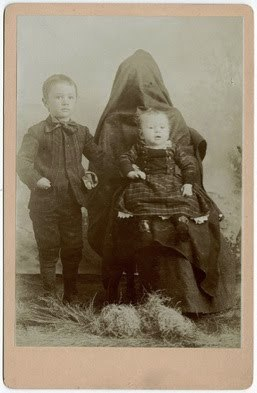 "The ""Hidden Mother"" is a type of 19th century photo where a child is  photographed sitting in his or her mother's lap. Later, the photo is  matted or framed to hide the mother, leaving just the calm child in  view. To make the cropping less obvious, the mother was sometimes  wrapped up in fabric.  Remove the frame or matte though and you're left  with a delightfully creepy photo."