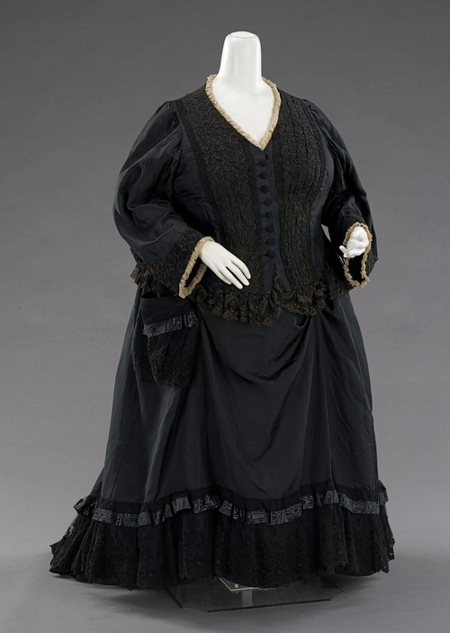 This dress was once worn by Queen Victoria (1819-1901) of the United Kingdom, as documented in an 1894 photograph of the Queen holding her great-grandson, Edward VIII (1894-1972). Purchased from an annual sale of the Queen's garments, it shows the traditional touches of mourning attire, which she wore from the death of her husband, Prince Albert (1819-1861), until her own death. The simple white trim and minimal use of crinkled crepe on the dress indicate a state of half mourning, although it is 33 years after her husband's death. The bodice is of a lighter material to allow for comfort during summer months and the entire garment is finely detailed inside and out.  1894, The Met