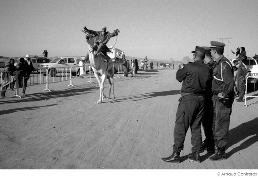 "Camel race. Day of joy for young tuaregs. Just another day for policemen coming from the north of Algeria. As most of people are happy to hit the road and go down south, for the ""green and blue"" boys, it's a punition, just like going to Siberia during the soviet period. Hoggar, Algeria, 2010"
