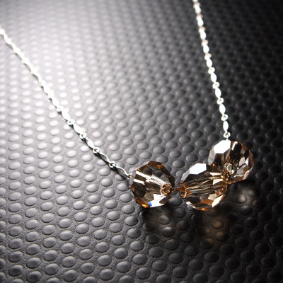 Xyla floating necklace with three oversize pale honey crsytals on flat bar sterling silver chain.