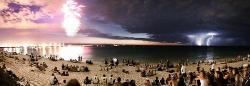 This was taken in Australia. Three separate things happening at once: On the left, fireworks exploded as part of Australia Day celebrations. In the middle, it's Comet McNaught. Then on the right, there's lightning from a thunderstorm far away.