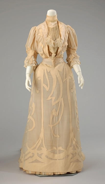 Wedding Ensemble | c. 1901 The appliqués of this wedding dress exemplify the whip-like curves and scrolls characteristic of the Art Nouveau period. Made in Rome for Mrs. Frederick Dand Sherman in 1901, the design of the dress shows the impact of the Art Nouveau movement throughout Europe by that year. While the white-on-white color palette would have been a conventional choice for a bride just after the turn of the century, the asymmetical trimming would have been a deliberately bold and fashion-conscious choice. The shape of the skirt and cut of the sleeves particularly suits the overall decorative scheme of the dress.